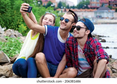 Best day of my friends. Three friends sitting and laughing at the river and pictures of each other on a cell phone