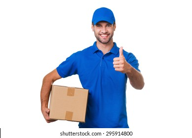 The best delivery service. Cheerful young courier holding a cardboard box and showing his thumb up while standing against white background