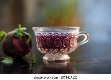 Best detoxify drink on a black glossy surface in a glass cup. Beetroot tea in a transparent glass cup on a black surface with a raw beet and some mint leaves. Horizontal shot with blurred background.