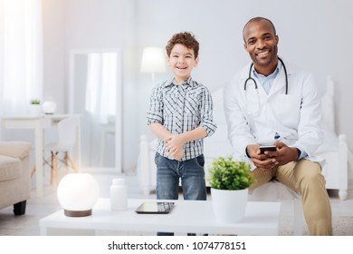 Best doc. Afro American positive male doctor wearing uniform while grinning and boy standing next to him