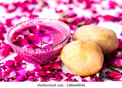 Best face mask or face pack to reduce blemishes and dark patches isolated on white i.e. Rose petals well mixed with potato juice in a bowl and raw potato and rose petals present on the surface.