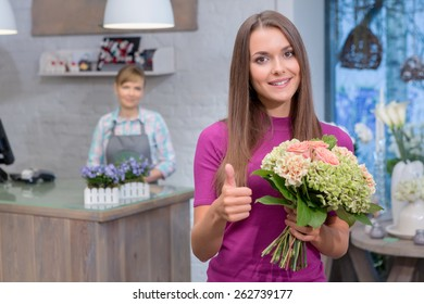 Best flowers for special occasion. Attractive young woman holding a bouquet raises her thumb up showing satisfaction with the purchase