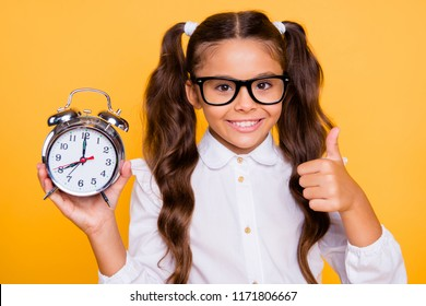 Best free time advertising concept. Close up portrait of confident, pretty, charming, lovely, sweet, gorgeous, small girl isolated on yellow background with big alarm clock in her hands show or give