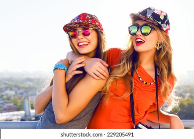 Best friend having fun on the roof, going crazy together, wearing floral swag hats and mirrored sunglasses, amazing view on the city, bright colors evening sunlight.