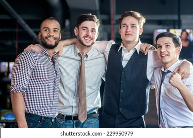 Best Friends in the bar. Four friends standing arm in arm at the bar and look at the TV