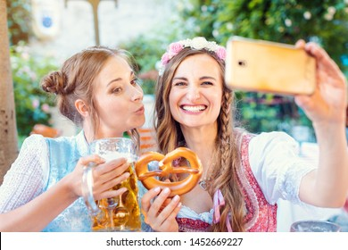 Best friends in Bavarian Tracht making a Selfie with the phone, beer, and a pretzel