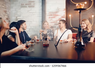 Best friends boys and girls meet in Shisha cafe, drink tea, chat, smoke hookah, laugh. Relaxed atmosphere