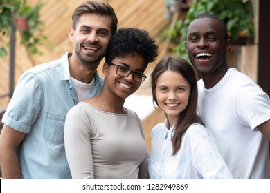 Best friends cheerful diverse people standing together smiling posing for camera. African and caucasian students millennial girls and guys enjoying time together. Concept of multi-ethnic friendship