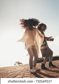 Best friends dancing and enjoying themselves outdoors. African females on road trip having fun.