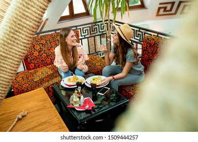 Best friends dining together and chatting in a restaurant