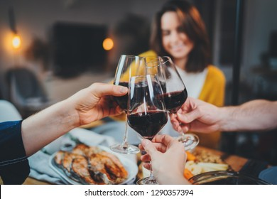 Best friends dining together in cozy home interior, group of people making cheers with glasses of red wine, Celebration Party Cheerful People Concept