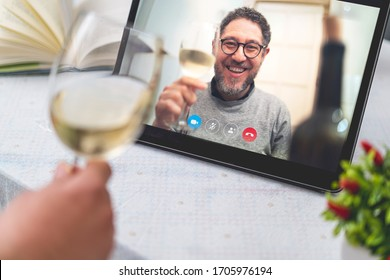 Best friends drinking and toasting online on a video call during the quarantine lockdown. Stay safe at home lifestyle concept.