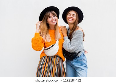 Best friends  embracing , couple of  stylish girls posing on white background. Fall season. Wearing stylish orange knitted sweater, black hat , bum bag. Friends spending great time together.