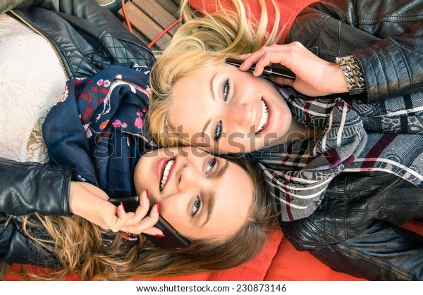 Best friends enjoying time together outdoors with smartphone - Concept of new technology with two girlfriends having fun on a vintage wood bench and red pillows - Desaturated retro filtered look
