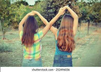 Best Friends Forever - two 12 year old teenage girls  holding hands in an infinity forever sign to signify BFF - vintage look