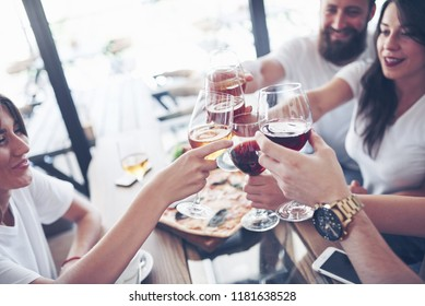 Best friends got together by table with delicious food with glasses of red wine to celebrate a special occasion.