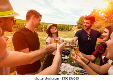 best friends have garden party with barbeque grilling and drinking rose wine beneath a vineyard. afternoon picnic in the field concept.  happy cheerful people's lifestyle concept.
