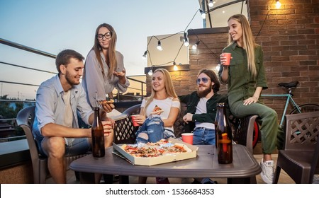 Best friends having Friday beer and pizza on a terrace lit by sunset sun
