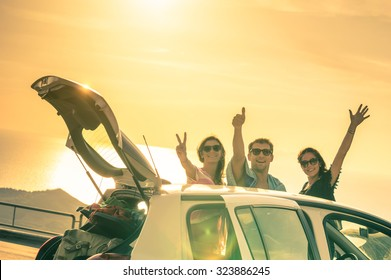Best friends having fun and cheering by car road trip at sunset - Group of happy people outdoor on vacation tour - Friendship and youth concept at travel together with positive nostalgic emotions