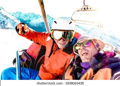Best friends having fun taking selfie at chairlift with snowboard equipment on mountain ski resort - Winter friendship concept with young people ready to ride down the slope - Bright vivid filter