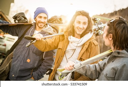 Best friends having fun together walking after ski and snowboard at mountain trip - Friendship concept with young people hangout loving winter sports travel - Warm filter with backlight sunshine halo