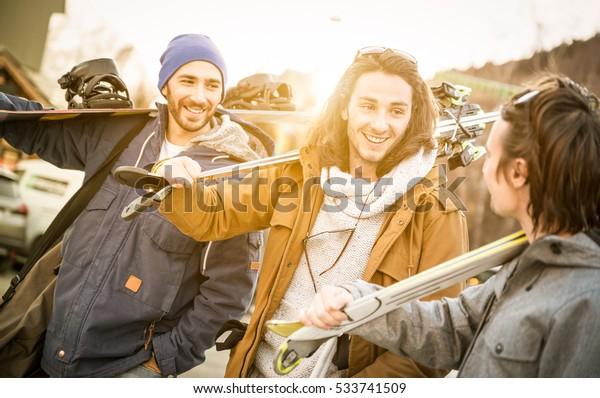 Beste Freunde, die sich bei der Bergtour gemeinsam mit Ski- und Snowboard-Wanderung amüsieren - Freundschaftskonzept mit jungen Leuten, die Wintersportreisen lieben - Warmfilter mit Hintergrundbeleuchtung, Sonnenschein