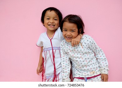 Best friends having fun, Two happy little Asian girls ,laughing on pink background.