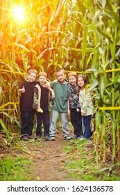 Best friends having fun in a typical American pumpkin patch corn maze during the fall season
