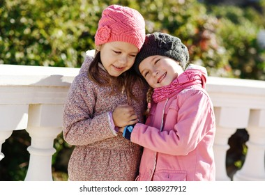the best friends are hugging outdoors and smiling