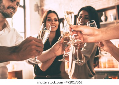 To the best friends! Low angle view of cheerful young people cheering with champagne flutes and looking happy while having party at home