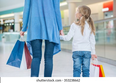 Best friends. Pleasant happy mother and daughter holding hands of each other and walking along mall while having shopping
