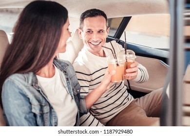 Best friends. Profile photo of pretty female that keeping smile on her face and touching glasses while sitting in car