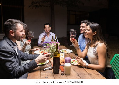 Best friends raising toast with wineglasses during dinner party in backyard