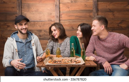 Best friends resting in pizzeria and big excitedly smiling. Three friends looking at their happy friend in cap and waiting for his reaction.