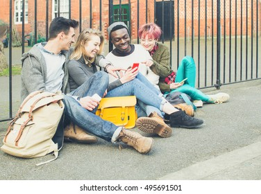 Best friends sitting on the sidewalk after university and having time chilling on phones. Social media people having fun looking on smartphone and smiling. Concept of cheer persons and friendship .
