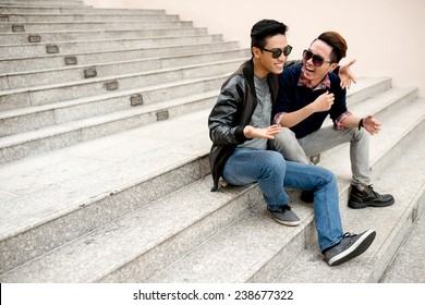 Best friends in sunglasses sitting on the steps and laughing
