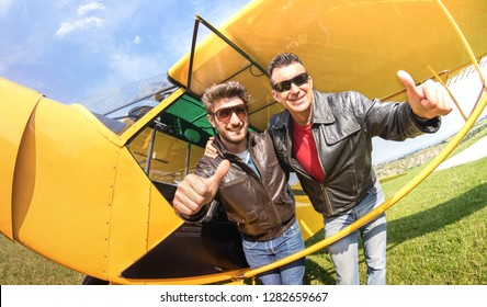 Best friends taking selfie at aeroclub by ultra light airplane - Luxury friendship concept about young happy people with thumbs up having fun together outside - Sunny afternoon vivid color tone filter