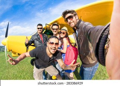 Best friends taking selfie at aeroclub with ultra light airplane - Happy friendship concept with young people having fun together outdoors - Sunny afternoon vivid color tones - Fisheye lens distortion