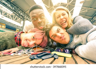 Best friends taking selfie indoors with back lighting - Happy friendship concept with young people having fun together - Warm vintage filtered look with focus on lower faces and sunshine halo flare
