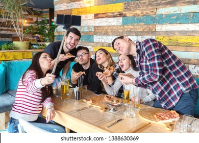 Best friends taking selfie at lunch party with funny faces - Happy friendship concept with young trendy people having fun together drinking beer and sharing pizza at bar restaurant