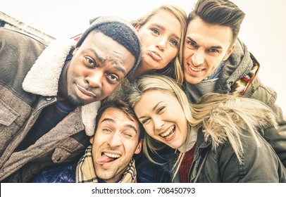 Best friends taking selfie outdoor on autumn winter clothes - Happy youth concept with multiracial people having fun together - Cheer and friendship against racism - Retro contrast desaturated filter