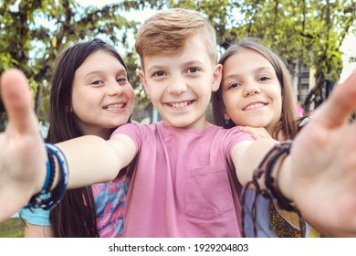 Best friends taking selfie outdoors in backyard – happy friendship with smart kids having fun celebrating summer vacation – modern children enjoying time together at garden party playing and smiling