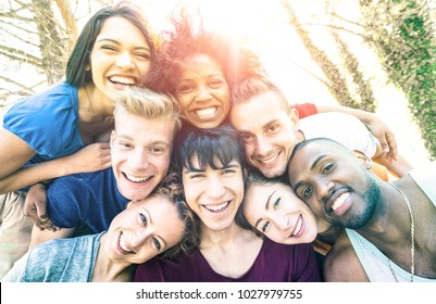 Best friends taking selfie at picnic with back lighting - Happy youth friendship concept against racism with young people having fun together - Vintage desaturated filter with sunshine halo flare