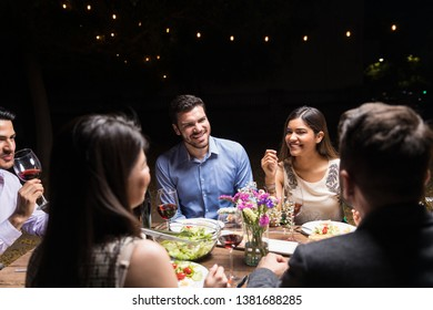 Best friends talking while having food and wine at dining table in restaurant