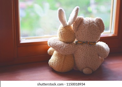 Best friends teddy bear and bunny toy sitting on brown window sill hugging each other and looking out of window. Love, family and friendship concept.