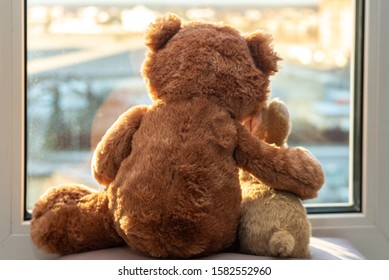 Best friends teddy bear and bunny toy sitting on window sill hugging each other and looking out of window. Love, family and friendship concept. stay at home, safe, quarantine