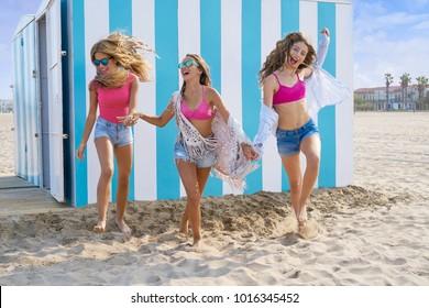 Best friends teen girls group running happy in a beach having fun