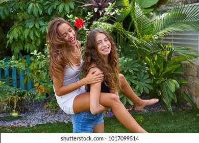 Best friends teen girls piggyback on backyard garden happy smiling