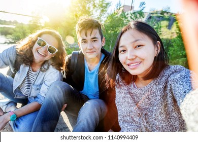 Best friends teenagers school friends taking selfie outdoors with backlighting - Happy friendship concept with young people having fun together
