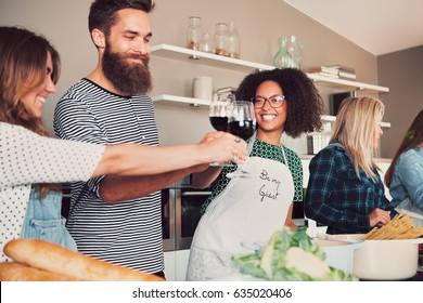Best friends toasting with wine in kitchen to celebrate their companionship in food preparation